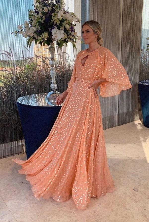 vestido de festa longo laranja claro com estampa de bolinhas douradas para casamento durante o dia