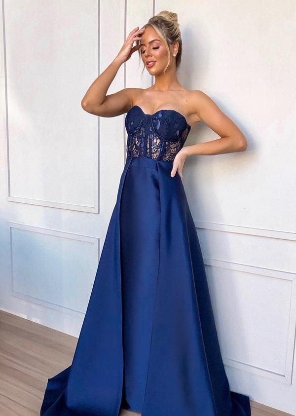 Vestido de festa azul marinho com corpete rendado e decote tomara que caia.