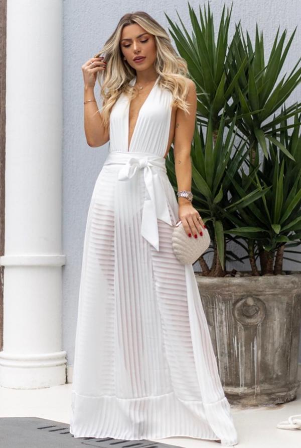 Mayara Castilho de vestido branco longo com uma leve transparência na saia e hot pants.