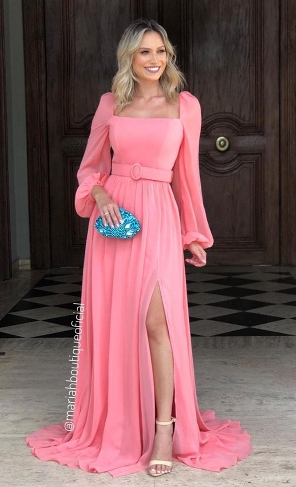 Vestido rosa com mangas bufantes longas, fenda e cinto do mesmo tecido do vestido.